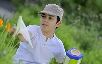 Boy in brown hat swatting a net to catch a butterfly in a field