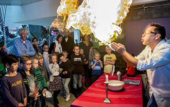 Mad scientist blowing fire out of his hands in front of children