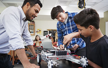 Teacher with male students building robotic vehicle
